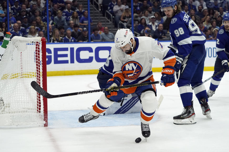 New York Islanders right wing Jordan Eberle, front, hits the puck with his foot in front of Tampa Bay Lightning defenseman Mikhail Sergachev (98) during the first period in Game 5 of an NHL hockey Stanley Cup semifinal playoff series Monday, June 21, 2021, in Tampa, Fla. (AP Photo/Chris O'Meara)