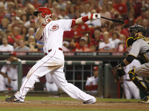 Cincinnati Reds' Todd Frazier, left, hits a three-run home run off Pittsburgh Pirates starting pitcher Charlie Morton during the sixth inning of a baseball game, Saturday, July 12, 2014, in Cincinnati. Pirates catcher Russell Martin watches at right. .(AP Photo/David Kohl)