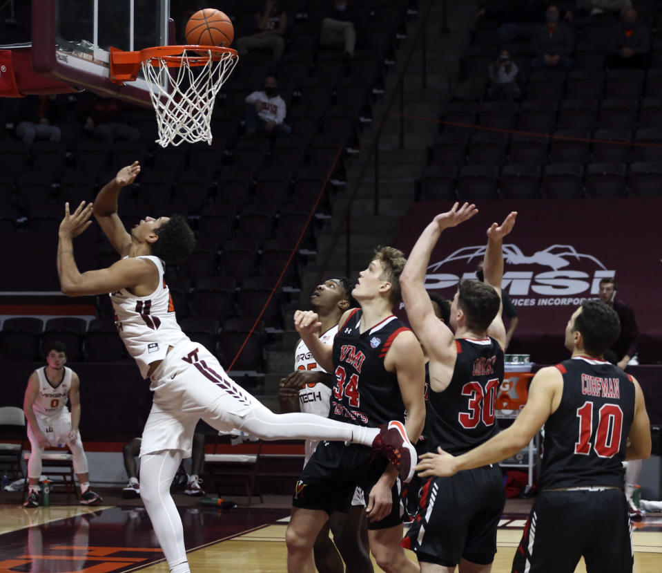 Virginia Tech's Keve Aluma (22) scores after driving into the lane past VMI's Jake Stephens (34) Sean Conway (30) and Kamdyn Curfman (10) during the second half of an NCAA college basketball game, Thursday, Dec. 3, 2020 in Blacksburg, Va. (Matt Gentry/The Roanoke Times via AP, Pool)