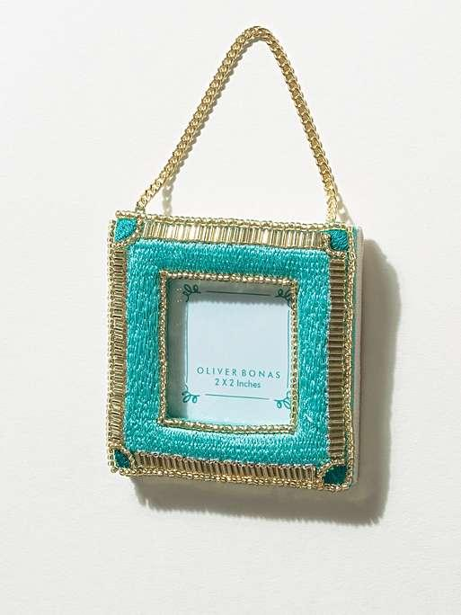 """<h3><a href=""""https://www.oliverbonas.com/us/homeware/beaded-aqua-mini-hanging-photo-frame-2x2-251477"""" rel=""""nofollow noopener"""" target=""""_blank"""" data-ylk=""""slk:Oliver Bonas Beaded Hanging Frame"""" class=""""link rapid-noclick-resp"""">Oliver Bonas Beaded Hanging Frame</a></h3><br>Table frames may be mundane, but hanging beaded picture keepers are gift catnip — hang them from windows, walls, or holiday trees. <br><br><strong>Oliver Bonas</strong> Beaded Hanging Photo Frame 2x2"""", $, available at <a href=""""https://www.oliverbonas.com/us/homeware/beaded-aqua-mini-hanging-photo-frame-2x2-251477"""" rel=""""nofollow noopener"""" target=""""_blank"""" data-ylk=""""slk:Oliver Bonas"""" class=""""link rapid-noclick-resp"""">Oliver Bonas</a>"""