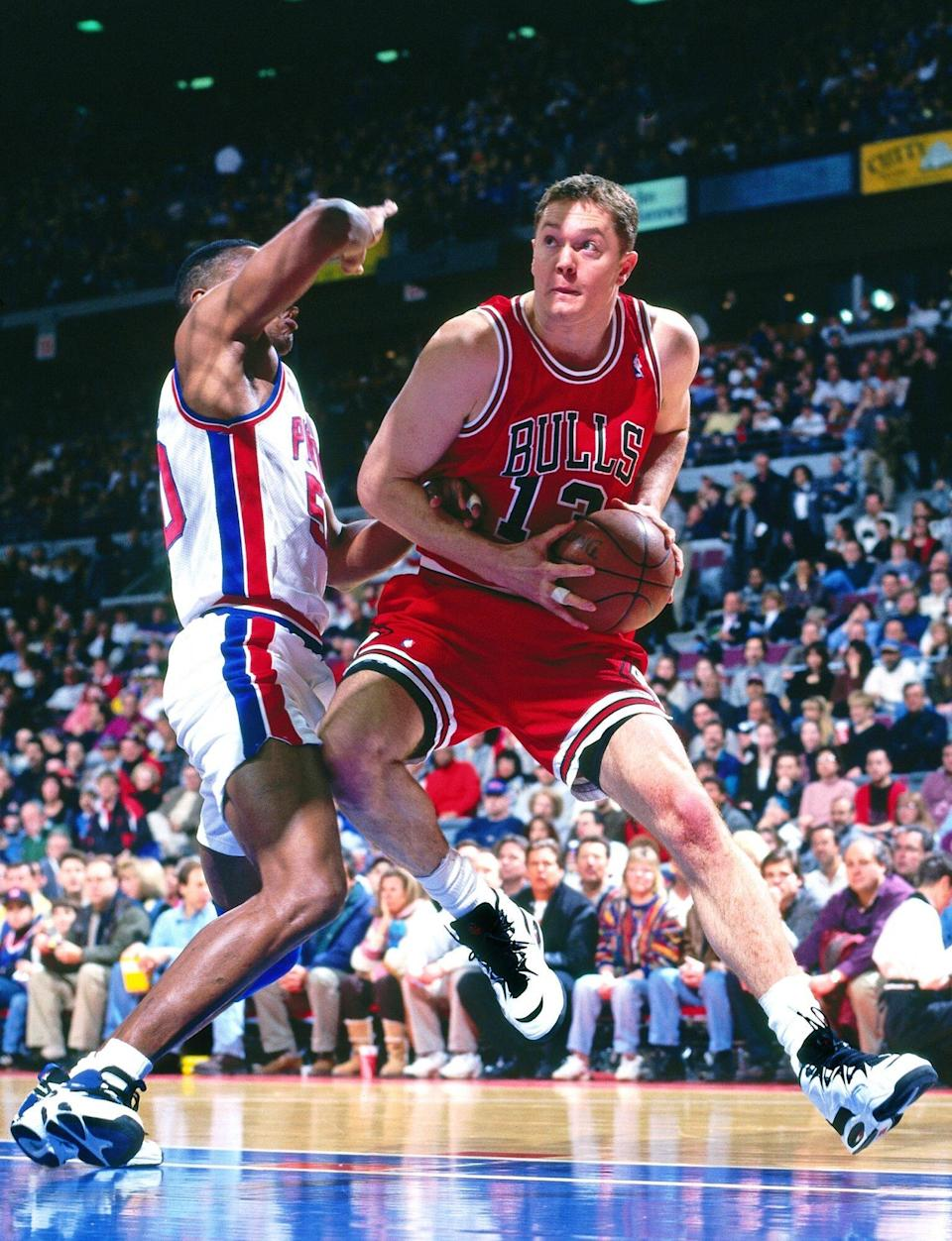 Luc Longley #13 of the Chicago Bulls drives against the Detroit Pistons on January 21, 1996 at the Palace of Auburn Hills in Auburn Hills, Michigan