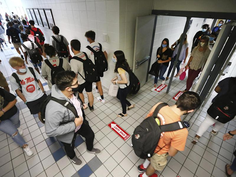 Students at Corinth High School follow the directional signage posted on the floor and keep foot traffic moving in the proper direction as they change classes on the first day back to school Monday 27 July 2020: (2020 The Associated Press)