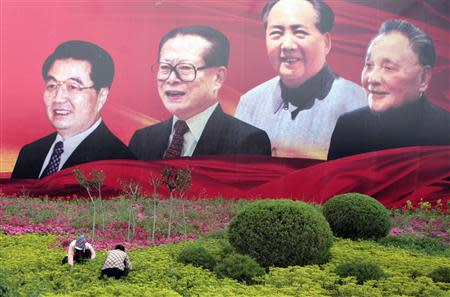Labourers work on a lawn in front of a billboard featuring Chinese leaders Hu Jintao, Jiang Zemin, Mao Zedong and Deng Xiaoping (L-R) on a street in Yinchuan, Ningxia Hui Autonomous Region in this July 10, 2009 file photo. REUTERS/Stringer/Files