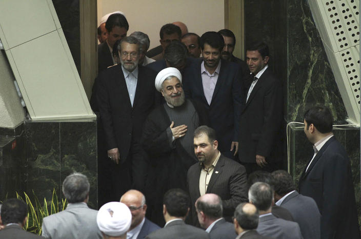 In this Sunday, July 14, 2013 photo released by the official website of the office of Iranian President-elect Hasan Rouhani, Rouhani, center, arrives for a meeting with lawmakers at the parliament, in Tehran, Iran. The Iranian president's inner circle brings more than new names to the Islamic Republic's power structures _ the group of advisers and allies also carries an array of degrees from Western universities. Few doubt that Hasan Rouhani will bring a far calmer and more measured approach than his predecessor. What remains unclear is how much it could actually influence Iranian policies. (AP Photo/Office of the President-elect, Mohammad Berno)