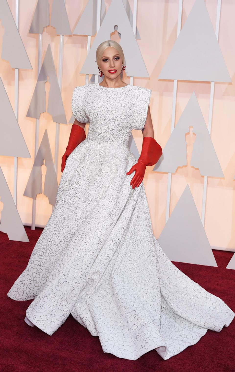 """Gaga wears a white gown by Alaia and <a href=""""http://stylecaster.com/best-memes-about-lady-gaga-red-gloves-at-2015-oscars/"""" target=""""_blank"""" rel=""""noopener noreferrer"""">a pair of meme-worthy red gloves</a> on the red carpet at the 2015 Oscars."""