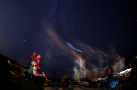 <p>People sit outside and watch as meteors speed past the Milky Way in Dwejra, Malta (Reuters) </p>