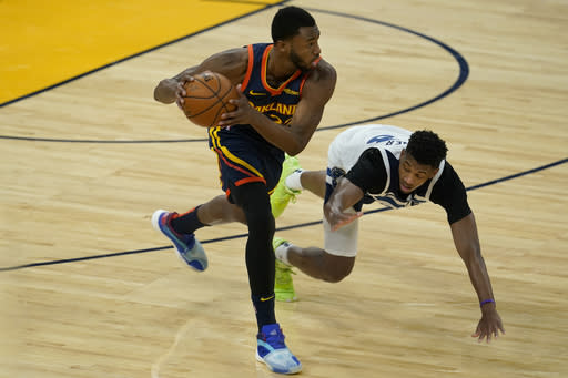 Golden State Warriors forward Andrew Wiggins, left, grabs the ball in front of Minnesota Timberwolves guard Jarrett Culver during the first half of an NBA basketball game in San Francisco, Monday, Jan. 25, 2021. (AP Photo/Jeff Chiu)