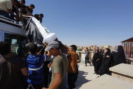 Mourners carry the coffin of Salah al-Wa'ili, a fighter from the Iraqi Shi'ite group Asa'ib Ahl al-Haq, during his funeral in Najaf July 12, 2014. REUTERS/Alaa Al-Marjani