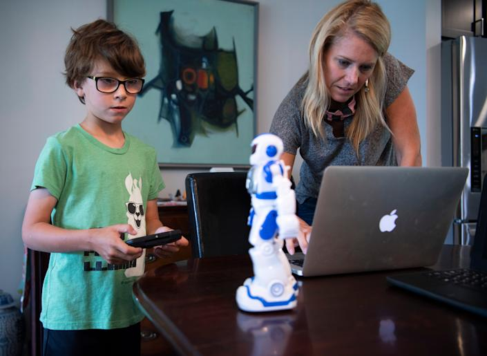 Heather Powell works to connect her son Hawkes to a lesson on their laptop from their home on the first day of school Tuesday, Aug. 4, 2020 in Nashville, Tenn.