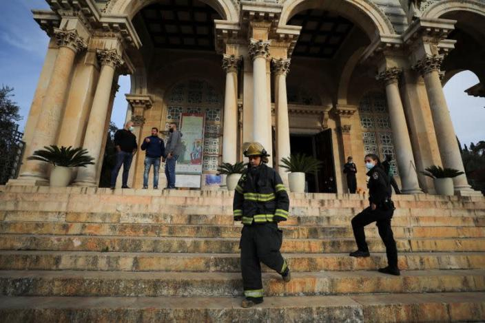 Israeli police and firefighters stand outside the Church of All Nations next to the Garden of Gethsemane after a man tried to set a fire inside the Church