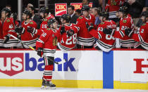 Chicago Blackhawks left wing Alex DeBrincat celebrates with teammates after scoring against the Nashville Predators during the first period of an NHL hockey game Wednesday, Jan. 9, 2019, in Chicago. (AP Photo/Kamil Krzaczynski)