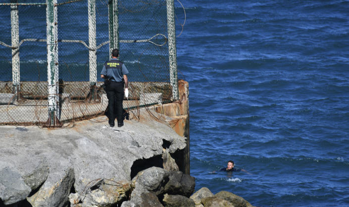 A Spanish Guardia Civil officer stands next to a man from Morocco who is swimming trying to cross into the Spanish territory at the border of Morocco and Spain, at the Spanish enclave of Ceuta on Monday, May 17, 2021. Authorities in Spain say that around 1,000 Moroccan migrants have crossed into Spanish territory (Antonio Sempere/Europa Press via AP)