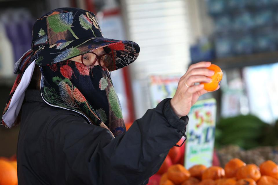 A shopper is seen wearing a face mask as they select fruit at a shop along Chapel Road in Bankstown in Sydney, Australia.