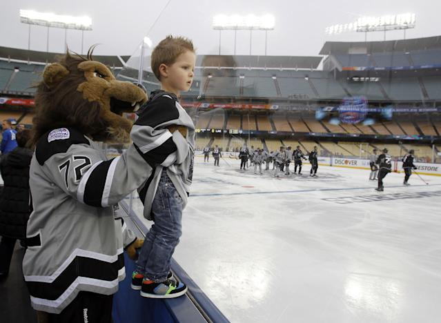 Calder Fraser, 3, looks for his father, Los Angeles Kings center Colin Fraser, with the Kings mascot, Bailey, during practice for the NHL Stadium Series hockey game, Friday, Jan. 24, 2014, in Los Angeles. The Los Angeles Kings and Anaheim Ducks will play outdoors at Dodger Stadium, Saturday. (AP Photo/Alex Gallardo)