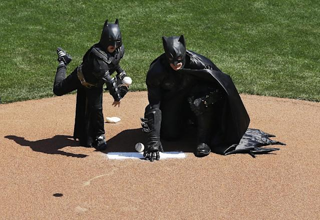 Miles Scott, dressed as Batkid, left, throws the ceremonial first pitch next to Batman before an opening day baseball game between the San Francisco Giants and the Arizona Diamondbacks in San Francisco, Tuesday, April 8, 2014. On Nov. 15, 2013, Scott, a Northern California boy with leukemia, fought villains and rescued a damsel in distress as a caped crusader through The Greater Bay Area Make-A-Wish Foundation. (AP Photo/Jeff Chiu)