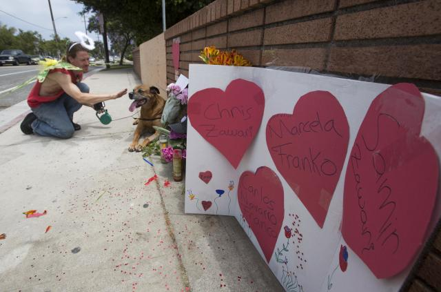 Hearts with messages placed by Nate Edelson, 39, a former student of Santa Monica College, dressed as a Fairly Angel, pets his dog Bull after putting heart-covered messages at a makeshift memorialat Santa Monica College Sunday, June 9, 2013, in Santa Monica, Calif. A shooting ramkpage that resulted in six deaths ended at the campus on Friday, (AP Photo/Ringo H.W. Chiu)