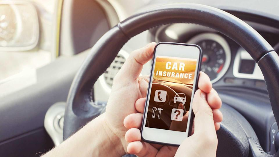 Driver reading car insurance website on smartphone