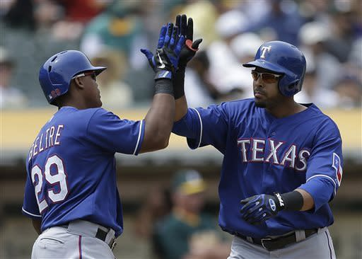 Texas Rangers' Nelson Cruz, right, celebrates with Adrian Beltre (29) after Cruz hit a three-run home run off Oakland Athletics' Jesse Chavez in the fifth inning of a baseball game Wednesday, May 15, 2013, in Oakland, Calif. (AP Photo/Ben Margot)