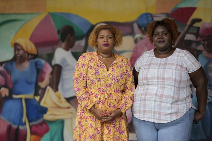Krystina Francois, left, and Francesca Menes, children of Haitian immigrants to the U.S. and co-founders of the Black Collective, pose for a picture in front of a mural at the Little Haiti Cultural Center, Tuesday, Sept. 21, 2021, in Miami. Menes and Francois, whose advocacy organization focuses on the political needs and economic empowerment of Black people across the African diaspora, have called for the Biden administration to immediately suspend plans to remove migrants via planes bound for Haiti. (AP Photo/Rebecca Blackwell)