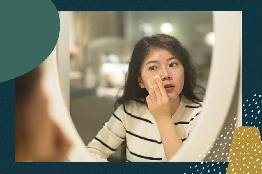Oriental lady putting on makeup in front of a mirror