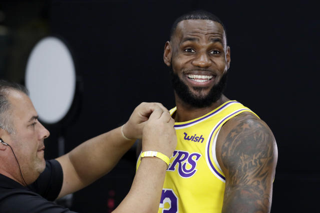 FILE - In this Monday, Sept. 24, 2018, file photo, Los Angeles Lakers' LeBron James smiles as a microphone is placed on his chest during media day at the NBA basketball team's practice facility in El Segundo, Calif. James says he didn't choose the Lakers as his free-agent destination because of his burgeoning career as a Hollywood producer and performer. He remains focused on basketball, and he wants to create a winning team to end the Lakers' franchise-record five years without a playoff berth. (AP Photo/Marcio Jose Sanchez, File)