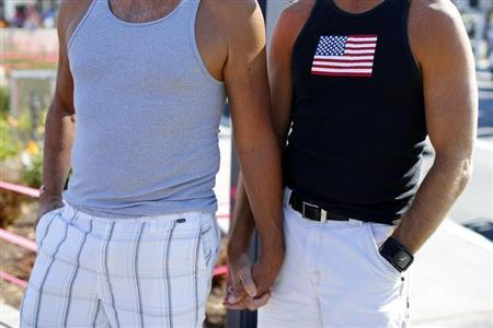 A gay couple holds hands during a rally in support of the United States Supreme Court decision on marriage rights in San Diego