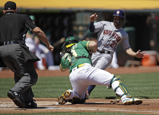 Houston Astros' Jose Altuve, right, is tagged out by Oakland Athletics catcher Josh Phegley in the first inning of a baseball game Sunday, Aug. 18, 2019, in Oakland, Calif. (AP Photo/Ben Margot)