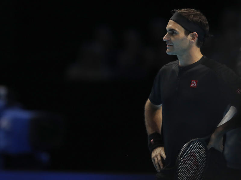 Switzerland's Roger Federer talks to the umpire as he plays against Austria's Dominic Thiem during their ATP World Tour Finals singles tennis match at the O2 Arena in London, Sunday, Nov. 10, 2019. (AP Photo/Alastair Grant)