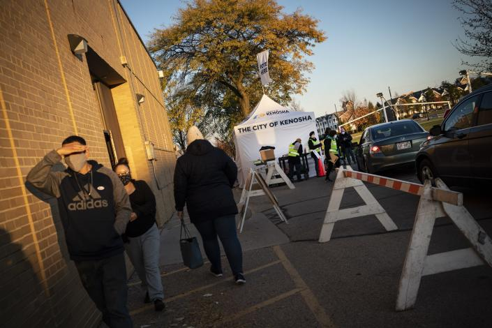 People leave Kenosha's municipal offices for early voting while cars wait in line for drive-thru voting, Friday, Oct. 30, 2020, in Kenosha, Wis. President Donald Trump has made protest violence in Kenosha and other American cities, a key part of his re-election campaign, linking violence to Democrats and saying it would spread dramatically if Democratic nominee and former Vice President Joe Biden was to defeat him on Election Day. (AP Photo/Wong Maye-E)
