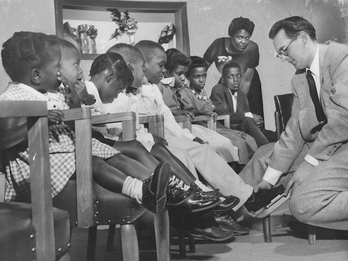 Helen Arnold watches as Gene Schroeter, manager of the children's shoe department at Yeager's, measures eight of the Arnold kids for new footwear in December 1957. Pictured from left are Donna, 20 months, Gerald, 3, Carla, 4, Gary, 6, John, 8, Gale, 9, Mona, 10, and Royal, 12. Oldest child Cathy, 15, was ill and couldn't be present for the photograph.
