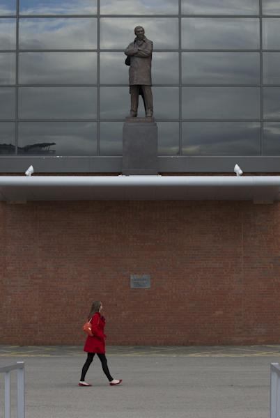 A member of the public looks up at a statue of manager Sir Alex Ferguson at Manchester United's Old Trafford Stadium, Manchester, England, Wednesday May 8, 2013. Alex Ferguson is retiring at the end of the season, bringing a close to a trophy-filled career of more than 26 years at Manchester United that established him as the most successful coach in British football history. (AP Photo/Jon Super)