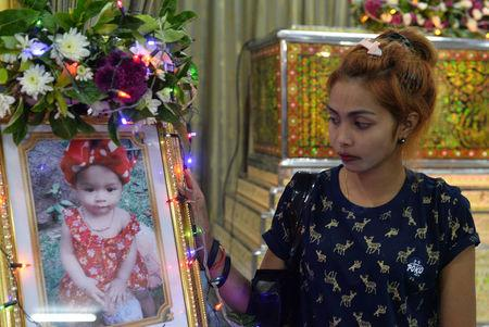 Jiranuch Trirat, mother of 11-month-old daughter who was killed by her father, stands next to a picture of her daughter at a temple in Phuket