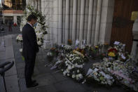 A man pays respect to the victims in front of Notre Dame church in Nice, France, Friday, Oct. 30, 2020. A new suspect is in custody in the investigation into a gruesome attack by a Tunisian man who killed three people in a French church. France heightened its security alert amid religious and geopolitical tensions around cartoons mocking the Muslim prophet. (AP Photo/Daniel Cole)