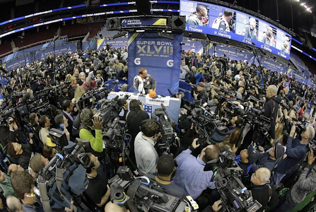 Denver Broncos' Peyton Manning is surrounded as he answers questions during media day for the NFL Super Bowl XLVIII football game Tuesday, Jan. 28, 2014, in Newark, N.J. (AP Photo/Charlie Riedel)