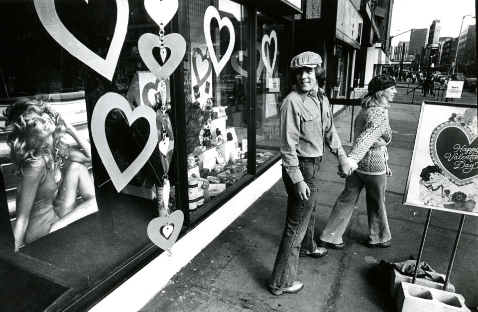 Lisa Joy-Clausen leads Alan Cohen from temptation, in the form of a smiling Farrah Fawcett poster in a Boston store window in 1977. (Photo: Stan Grossfeld/The Boston Globe via Getty Images)