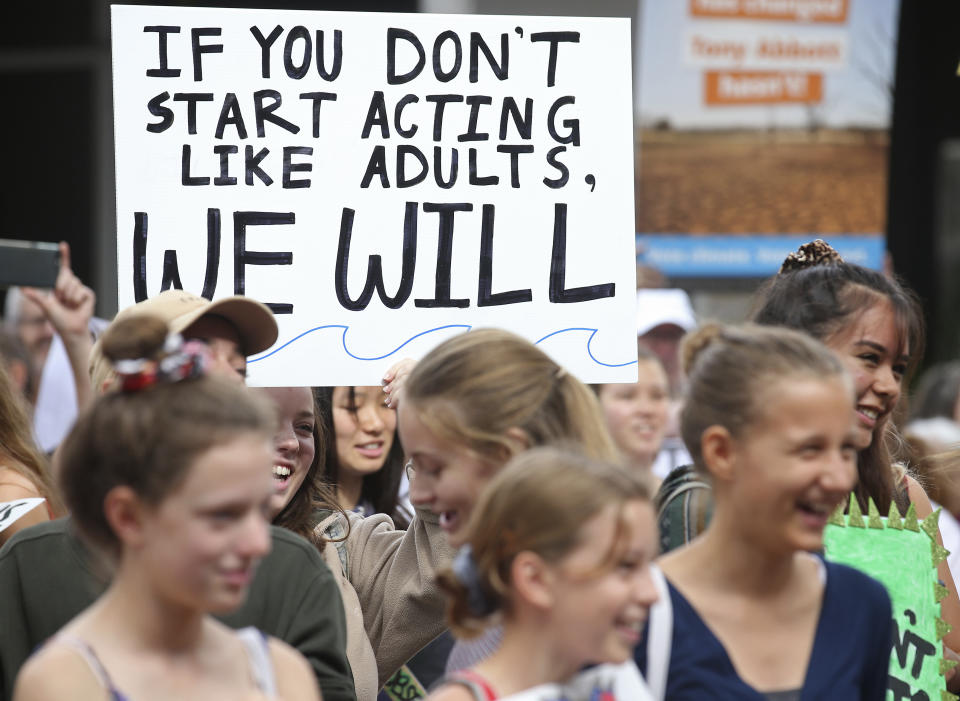 """Picturee of children at a Climate Strike rally in 2019, with one teen holding a sign saying """"If you don't start acting like adults, we will"""""""