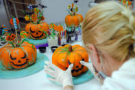 A woman, wearing a mask for protection against the COVID-19 infection, applies final decorations to Halloween themed sweets before they are shipped to customers at an upmarket deserts shop in Bucharest, Romania, Friday, Oct. 30, 2020. Romanians only started celebrating Halloween after the fall of the communist rule in 1989 and the feast's popularity kept growing every year. (AP Photo/Vadim Ghirda)