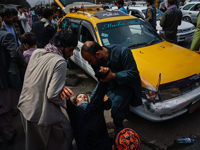 Men try to help a wounded woman after Taliban fighters maintained crowd control with lethal weapons