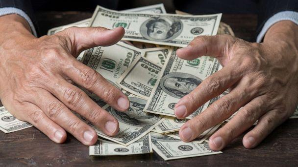 PHOTO: Man's hands sweep money. (Getty Images, STOCK PHOTO)