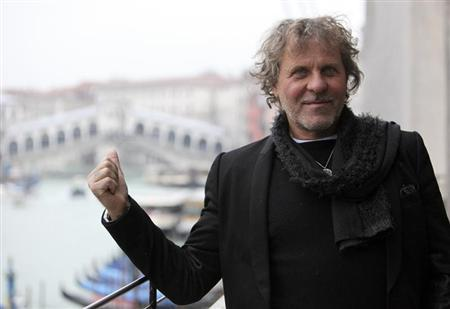 Founder of Diesel clothing company Renzo Rosso gestures as he poses in front of Rialto Bridge in Venice