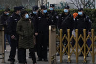 """Chinese police officers watch over a bus stop near the Great Hall of the People where the annual National People's Congress is held in Beijing on Friday, March 5, 2021. The ruling Communist Party is aiming for economic growth """"over 6%"""" as it rebounds from the coronavirus pandemic, Premier Li Keqiang said in a speech at China's ceremonial legislature Friday. (AP Photo/Ng Han Guan)"""