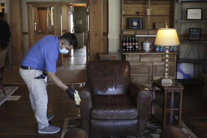 In this Thursday, May 28, 2020, photo, Aroldo Ramos, an employee at The Ocean Lodge, wipes down furniture in the hotel lobby with disinfectant in Cannon Beach, Ore. The Ocean Lodge welcomed guests back starting last week after an extended shut-down of all hotels and vacation rentals in the small beach town to prevent the spread of the new coronavirus. With summer looming, Cannon Beach and thousands of other small, tourist-dependent towns nationwide are struggling to balance fears of contagion with their economic survival in what could be a make-or-break summer. (AP Photo/Gillian Flaccus)