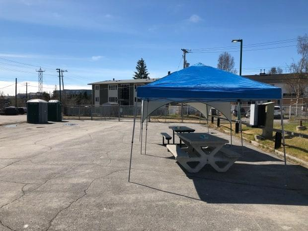 Picnic tables and portable toilets were set up in the parking lot next to Aspen Apartments on 51st Street after the temporary day shelter in downtown Yellowknife closed on Monday.  (Sidney Cohen/CBC  - image credit)