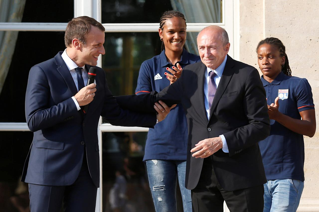 French President Emmanuel Macron (L) wishes a happy birthday to French Interior Minister Gerard Collomb (R) as Lyon's French captain Wendie Renard (C) applauds during a ceremony at the Elysee Palace in Paris, France, June 20, 2017 to celebrate the victory of Lyon's football team during the UEFA Women's Champions League.  Picture taken June 20, 2017.    REUTERS/Geoffroy van der Hasselt/Pool