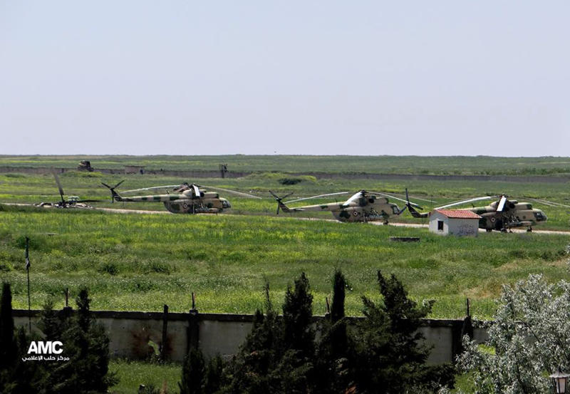 This citizen journalism image provided by Aleppo Media Center AMC which has been authenticated based on its contents and other AP reporting, shows Syran military helicopters at Mannagh air base in Aleppo province, Syria, Tuesday, June 18, 2013. Syrian warplanes bombed rebel positions near a contested military air base in the north of Syria on Tuesday, activists said, while President Bashar Assad's forces nearby pressed ahead with an offensive against opposition fighters in the country's largest city Aleppo. (AP Photo/Aleppo Media Center AMC)