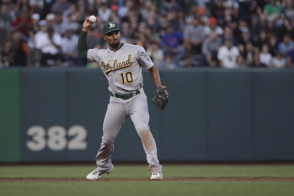 Oakland Athletics shortstop Marcus Semien throws out San Francisco Giants' Buster Posey at first during the fourth inning of a baseball game in San Francisco, Tuesday, Aug. 13, 2019. (AP Photo/Jeff Chiu)