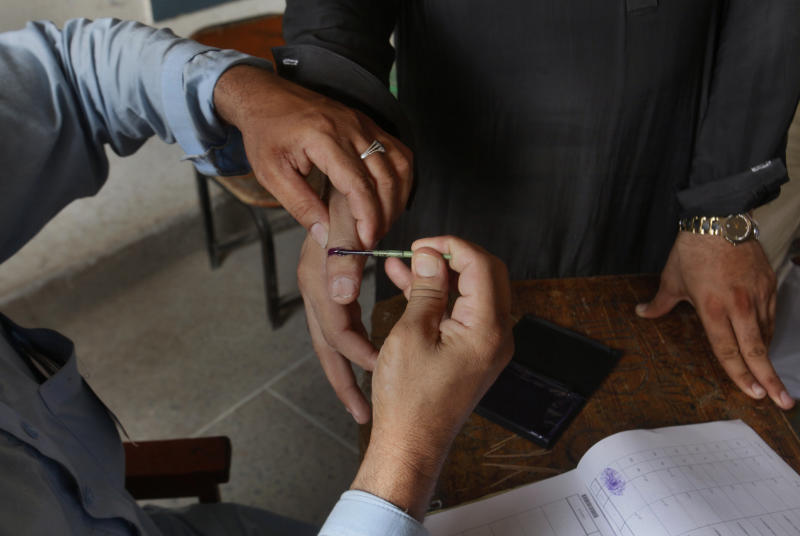 An election worker marks the thumb of voter in a polling station during an election for provincial seats in Jamrud, a town of Khyber district, Pakistan, Saturday, July 20, 2019. Pakistan's northwestern tribal areas are holding their first-ever provincial elections. The seven tribal areas were merged last year as tribal districts into the northwestern Khyber Pakhtunkhwa province. Before that, the tribal areas were federally administered, and residents could only vote in the national assembly. (AP Photo/Muhammad Sajjad)