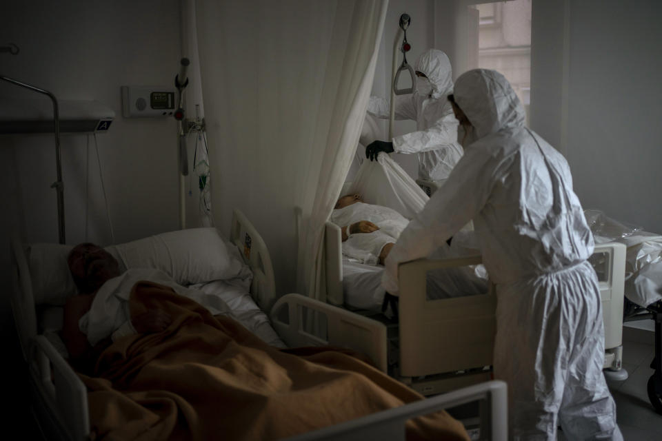 Wearing protective suits to prevent infection, funeral home workers remove the body of an elderly person who died of COVID-19 at a nursing home while another resident sleeps in his bed in Barcelona, Spain, Thursday Nov. 5, 2020. (AP Photo/Emilio Morenatti)