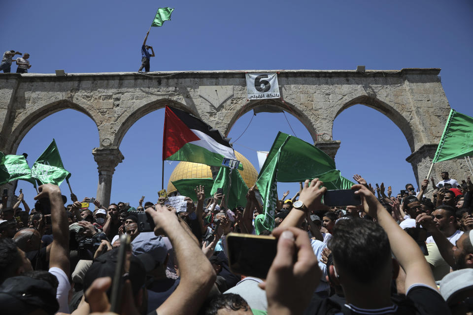 Worshippers wave Hamas and Palestinian flags during a protest against the likely evictions of Palestinian families from the homes, after the last Friday prayers of the Muslim holy month of Ramadan at the Dome of the Rock Mosque in the Al Aqsa Mosque compound in the Old City of Jerusalem, Jerusalem, Friday, May 7, 2021. (AP Photo/Mahmoud Illean)