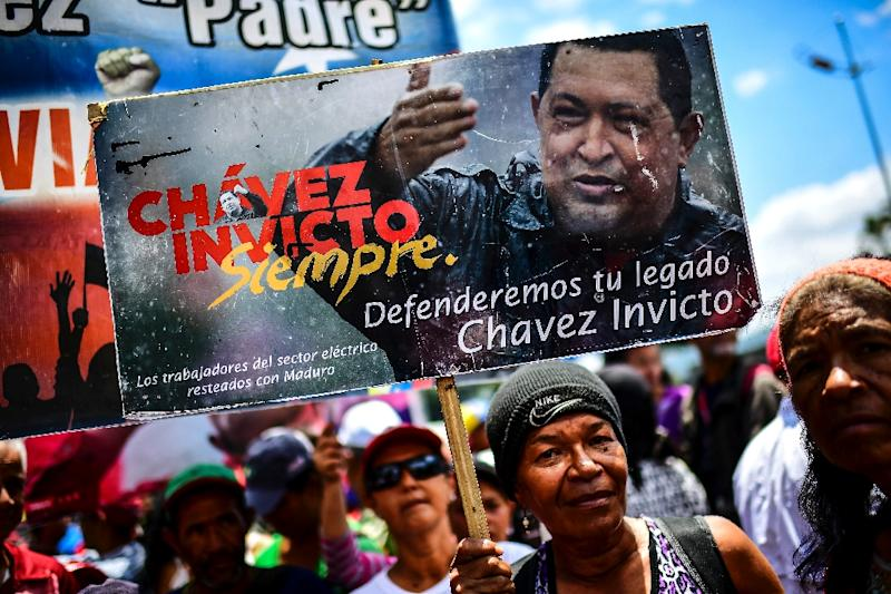 A supporter of Venezuelan President Nicolas Maduro holds an image of late Venezuelan president Hugo Chavez, during a demonstration in Caracas on March 16, 2019 (AFP Photo/RONALDO SCHEMIDT)
